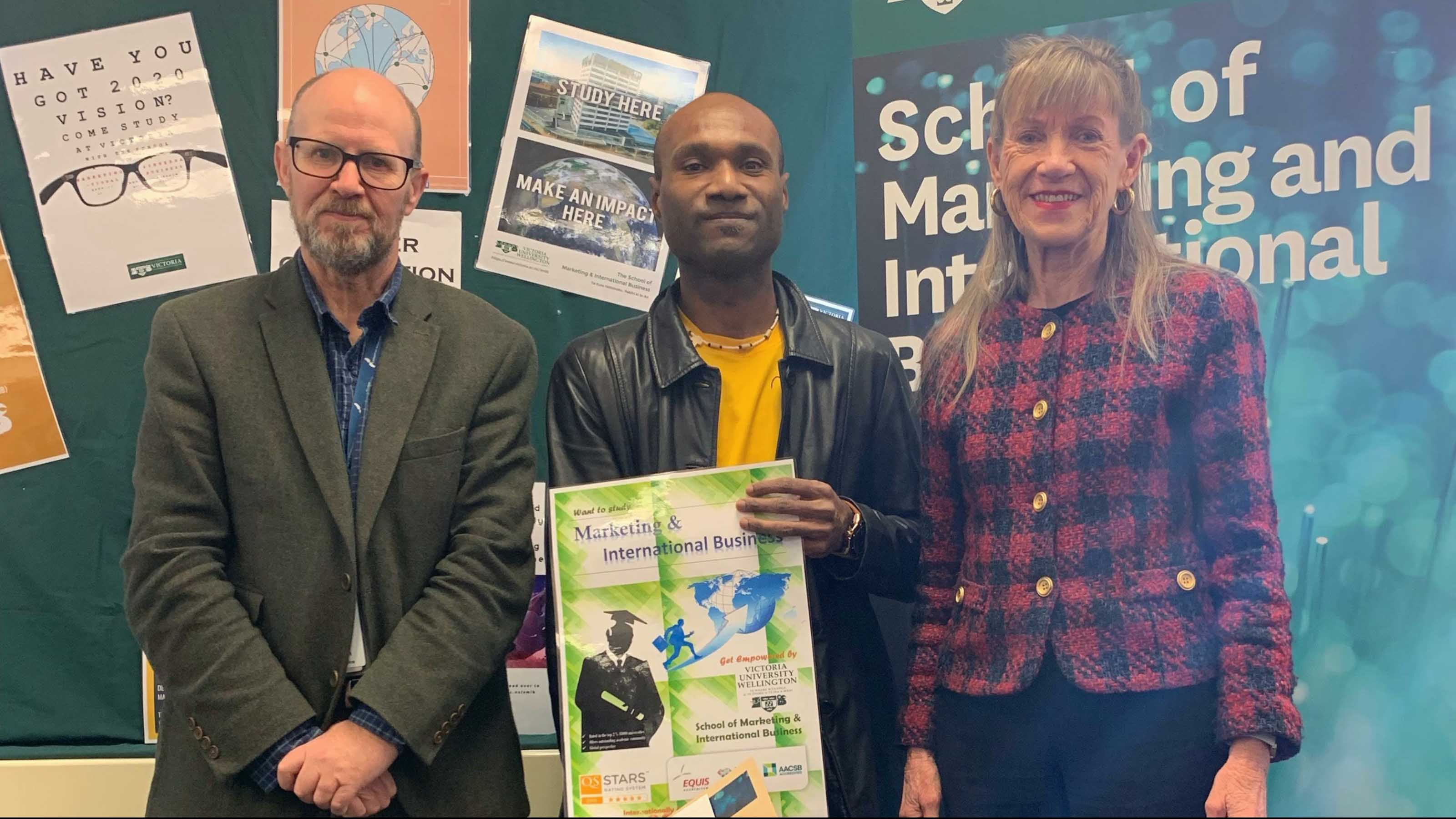 John Tulloch, Finalist Baptist Molai, and Val Hopper standing in front of the winning posters