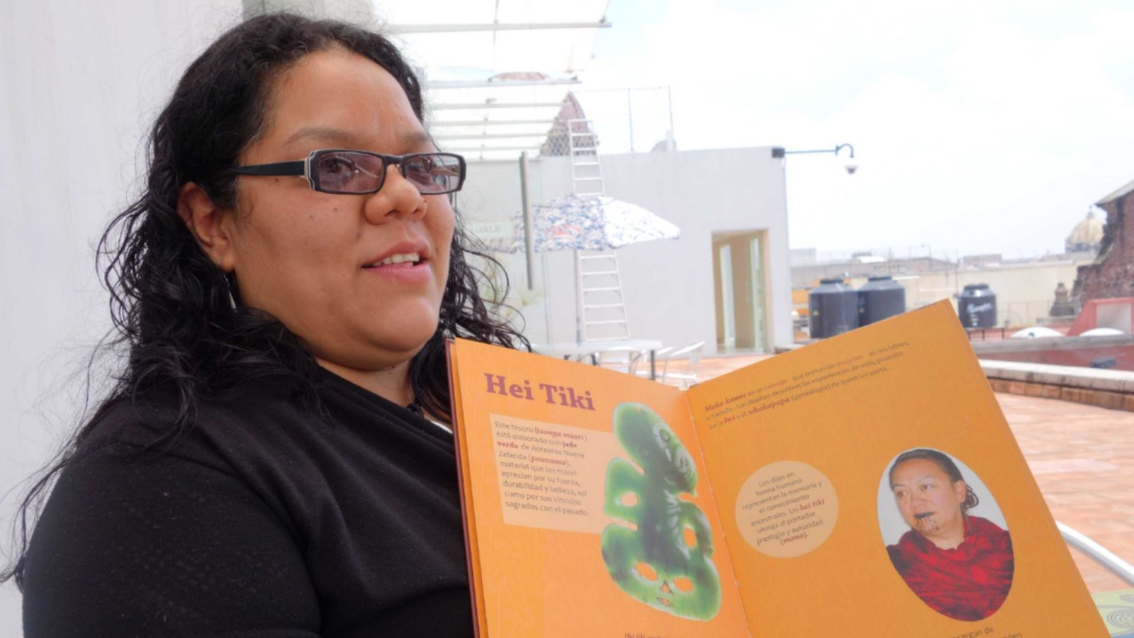 Monserrat Navarro holding a book resource she developed for Museo Nacional de las Culturas's showing of E Tū Ake