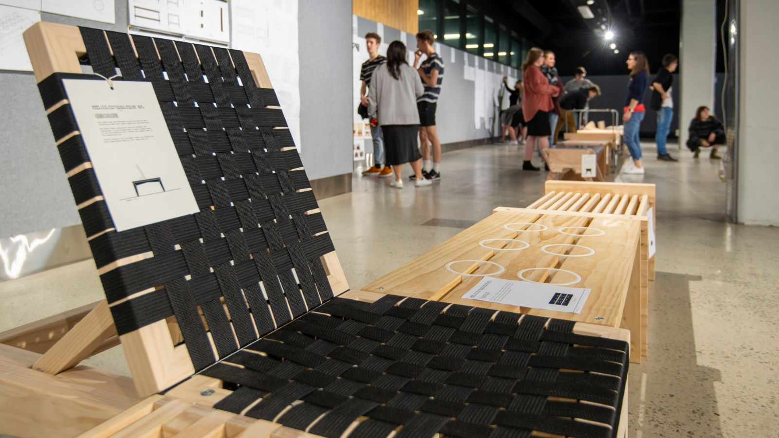 wooden bench with backrest and woven black fabric seat at front of exhibition of wooden furniture