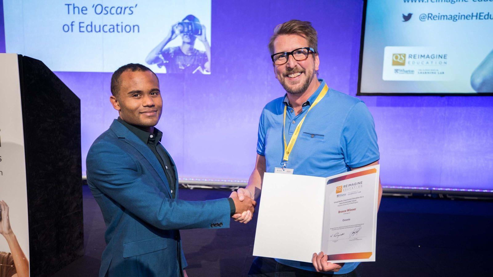 Christian Schott receives award at Reimagine Education Awards.