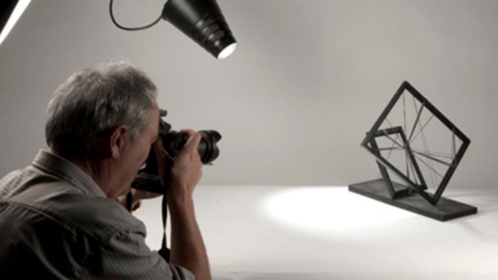 A man takes a photo of an abstract object in a photo studio