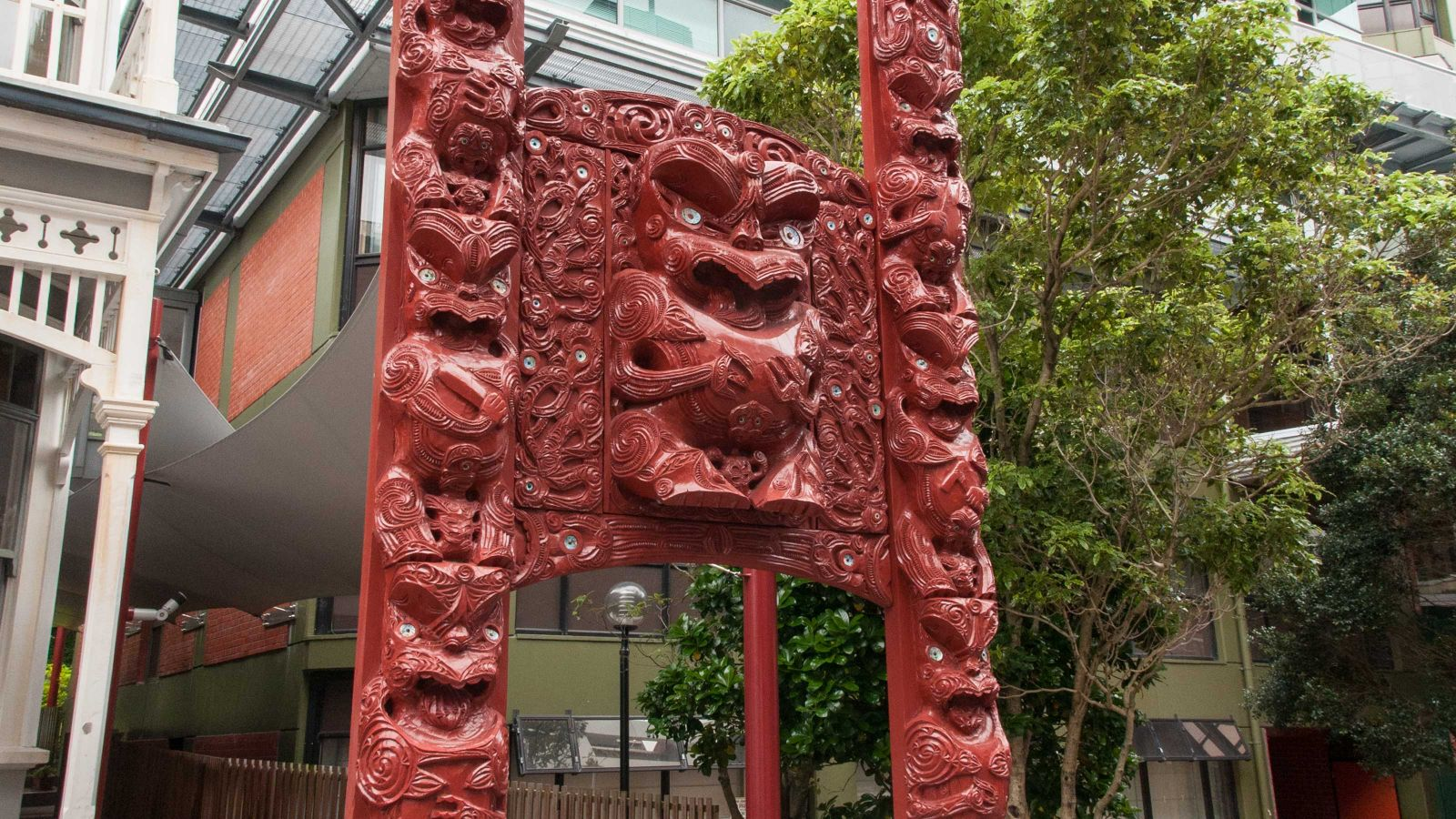 A tall red Māori carving with two pillars and a central section that opens with space at the bottom to allow for people to walk through.