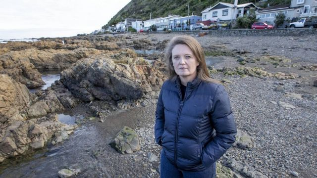 Phd candidate, Belinda Storey wearing a black jacket, standing on a beach in front of rocks on a cloudy day at Owhiro Bay. Houses and cars are on the street in the background. Photo: Monique Ford.