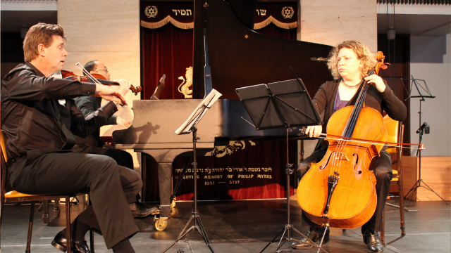 A man plays a violin and a woman plays a cello in the foreground with two music stands between them. Tucked in behind the violinist is a man playing a grand piano.