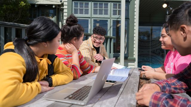 Five students sitting at a table outside Pasifika Haos and studying together.
