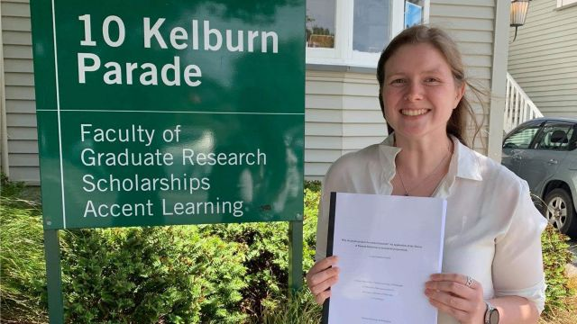 Lauren with a printed copy of her PhD thesis outside the Faculty of Graduate Research