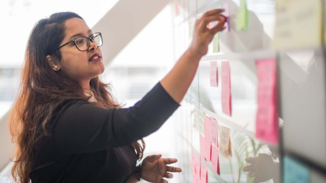 A student moves a post-it note on a kanban board.