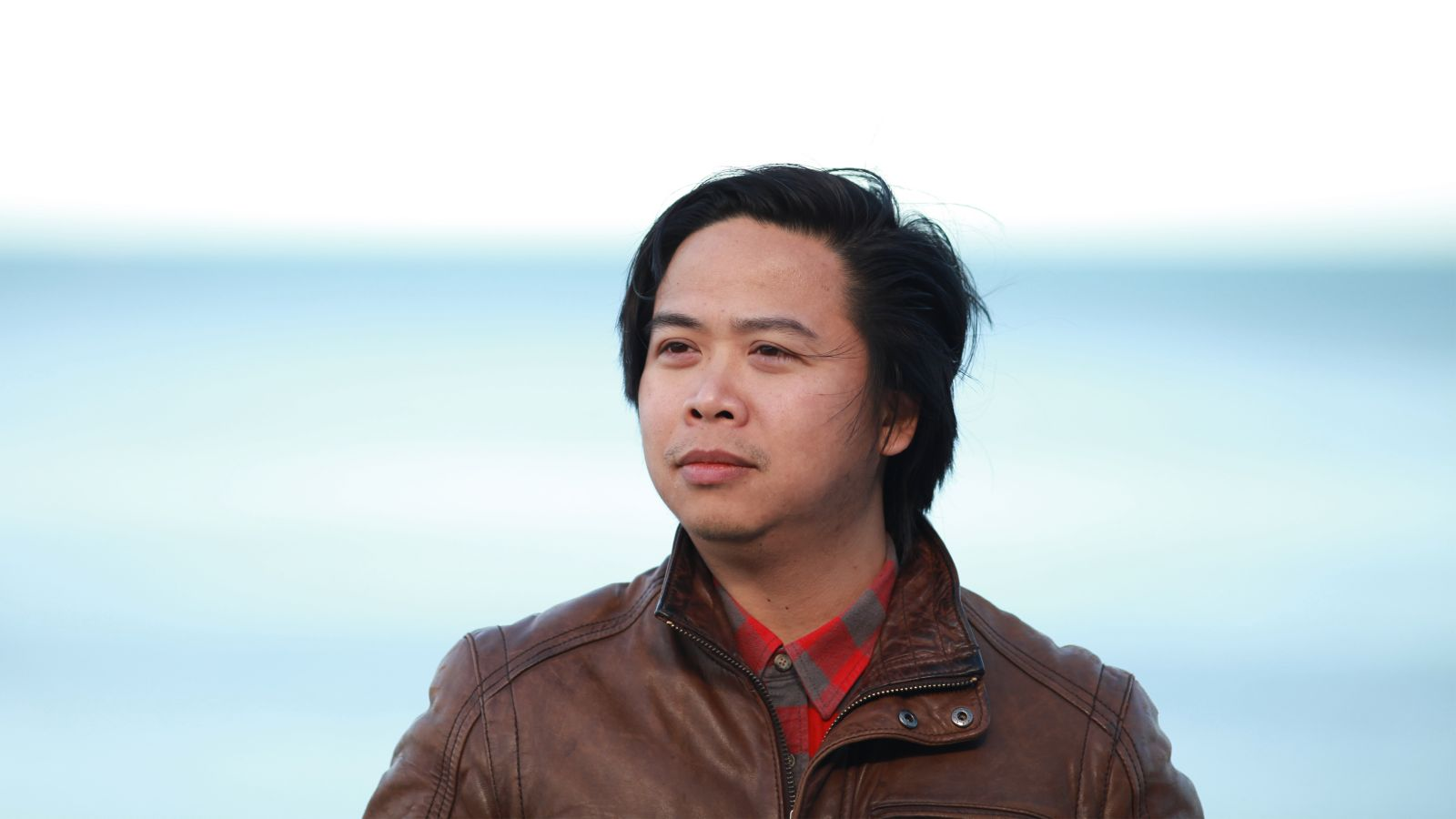 Quyet stands behind the ocean wearing a brown leather jacket looking away from the camera.