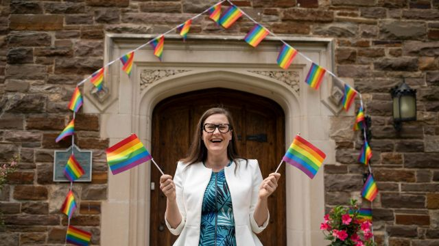Woman with blue dress holding two pride flags, in front of old building covered in rainbow coloured flags