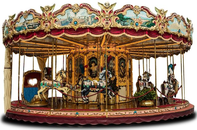 Victorian carousel fairground ride with red and gold accent colours. Roof is surrounded by landscape paintings in ornate panels alternating with cherubs. The centre column is covered with life-size portrait paintings. Horses and carriages with colourful decorations fill the carousel but no-one is riding them.