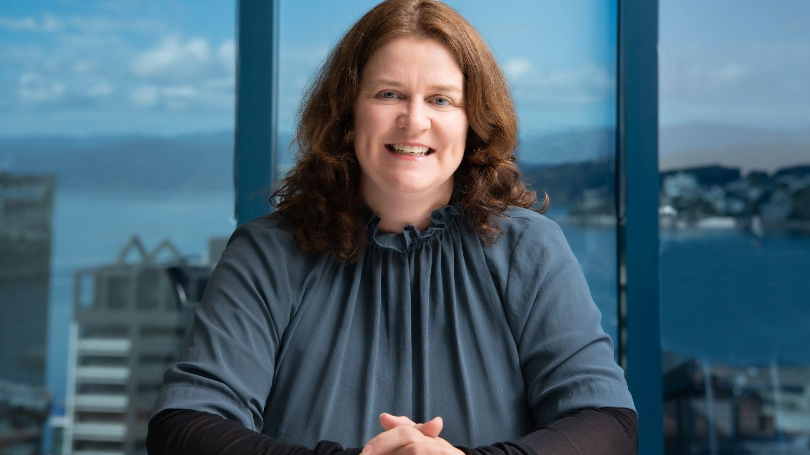 Portrait of distinguished alumna Stacey Shortall with a view of Wellington harbour behind her.