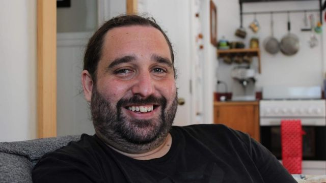 Man with stubble smiling with kitchen in background