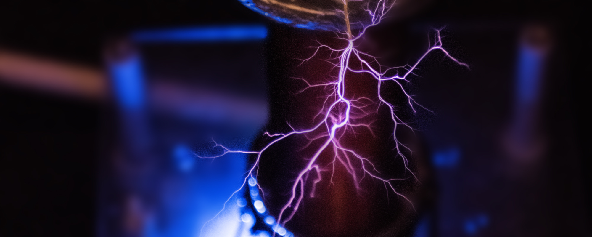 An image of pink electricity coming off of a tesla coil.
