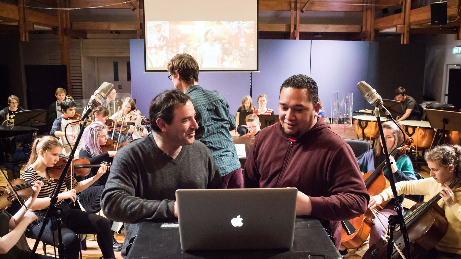 Music film scoring – A professor and a student look at a laptop, and stand between two freestanding microphones, while others play orchestral instruments in the background.