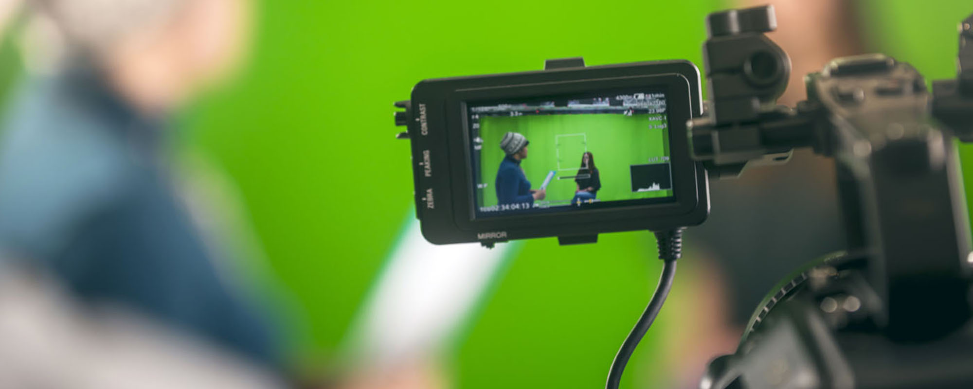 Film – A camera monitor shows two students working in front of a green screen.