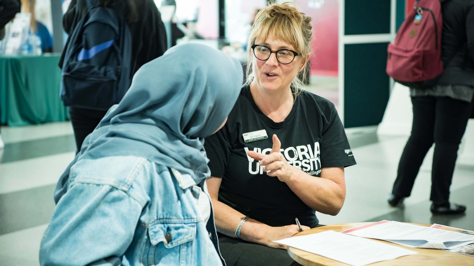 Blonde female careers consultant discussing a CV with Hijabi student in denim jacket