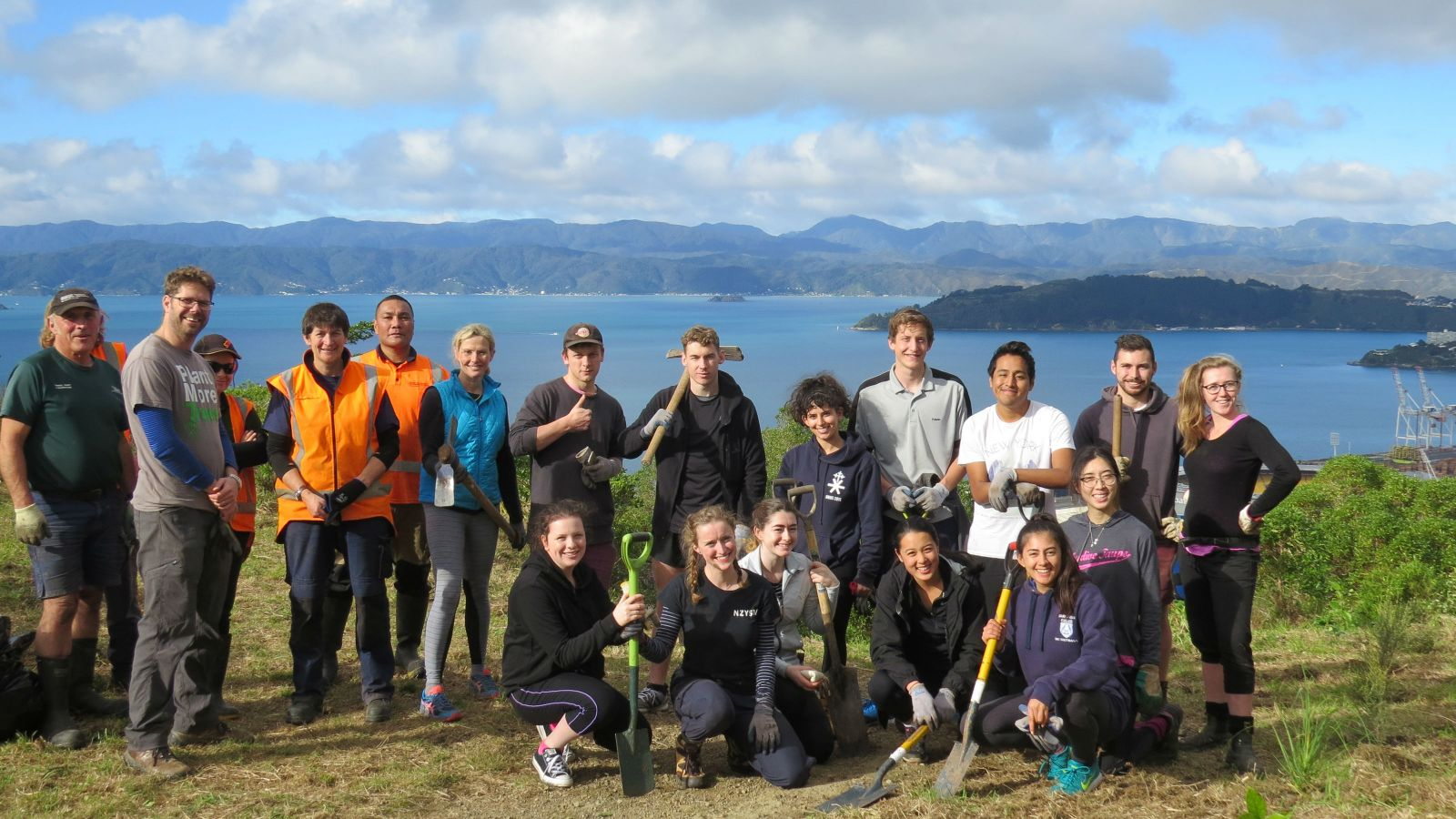 A group of student volunteers, hold landscaping tools while posing together on a hill with the ocean in the background.
