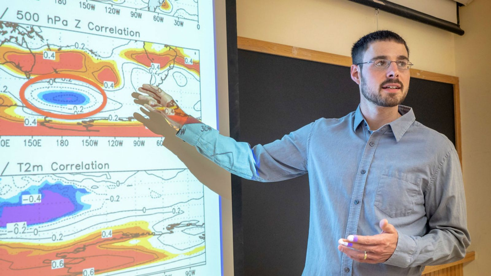 Kyle Clem stands in front of a map showing weather and pressure zones.