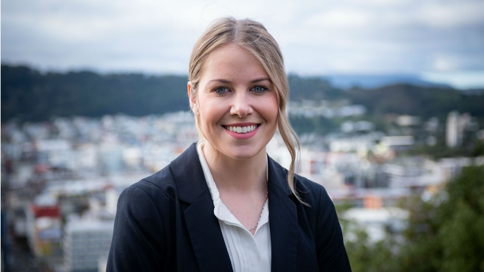 Laurette Siemonek stands outside with Wellington city behind her