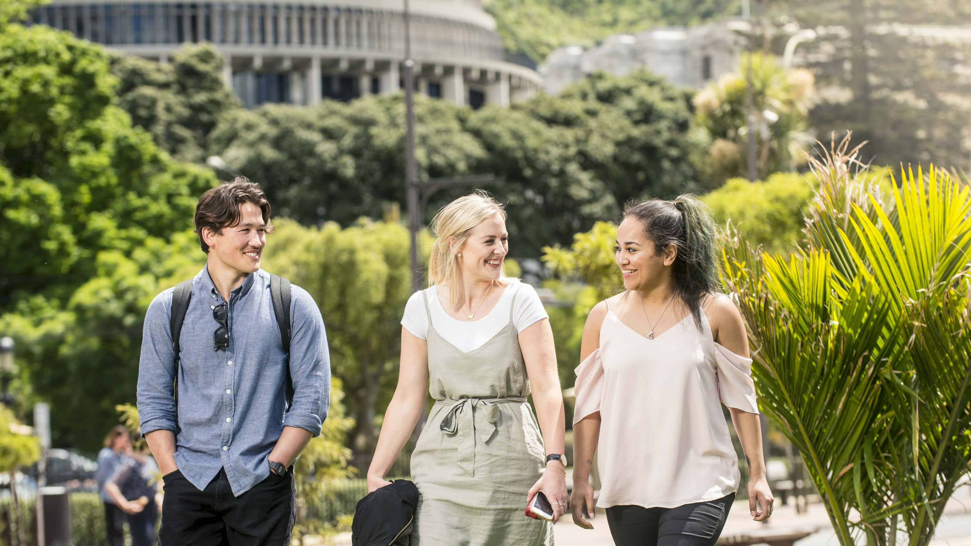 Three students walking past the Beehive, Parliament Buildings, in Wellington.