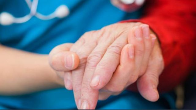 A close up of an older person holding hands with a carer
