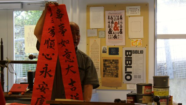 Calligrapher Stan Chan holds up a spring couplet.