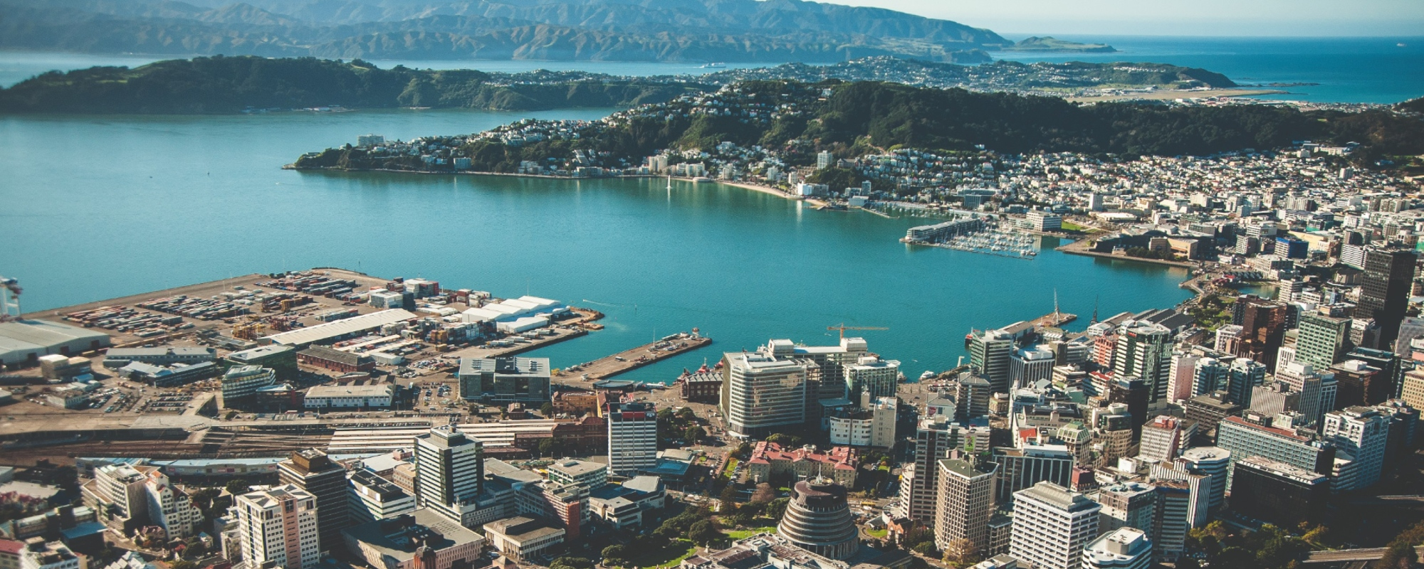 Aerial photo of Wellington showing central city and harbour on sunny day