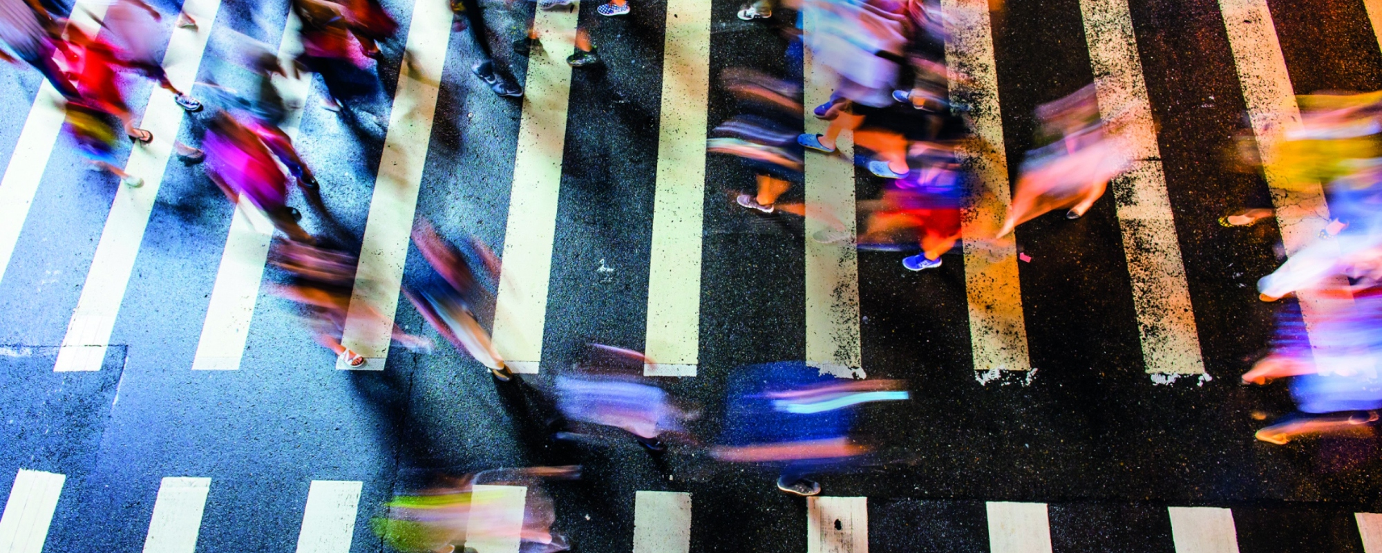 Birds eye view of several blurred people crossing both ways on a zebra crossing.