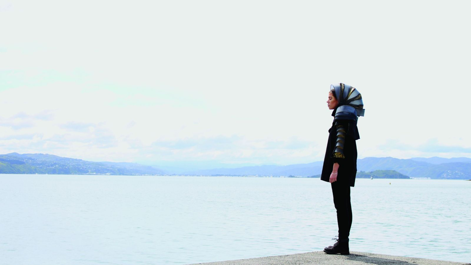 A woman in futuristic garb stands side on with Wellington Harbour in the background