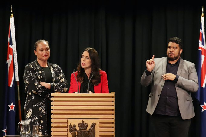 Jacinda Ardern speaking at a press conference with sign language interpreter to her left.