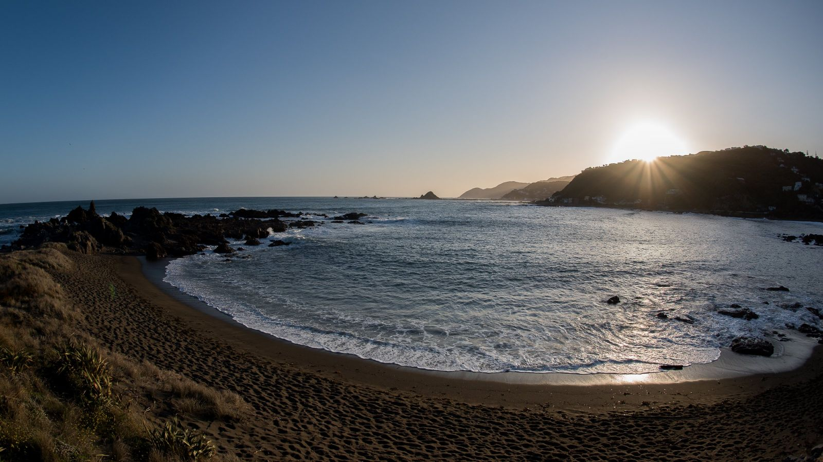 Sandy beach with rocks to the left going into the ocean, hills and sunrise in the distance. Clear blue sky