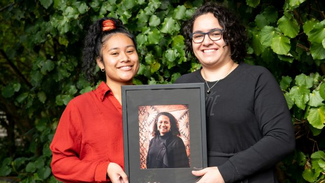 Kaitlin Abbot and Esther Patu, the two scholarship recipients, holding a framed picture of Teresia Teaiwa