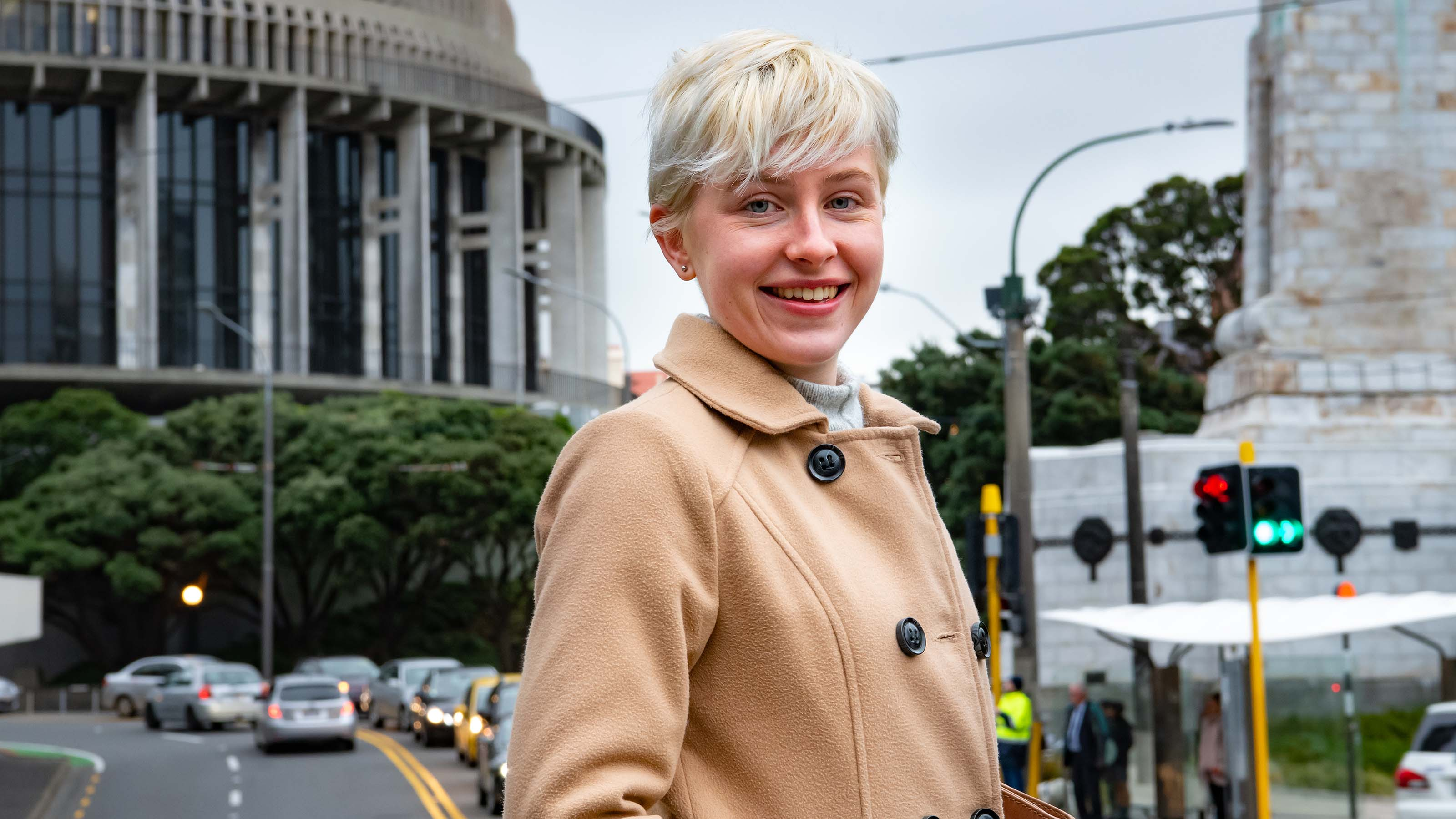 Student smiles while looking at the camera outside of the Beehive, one of New Zealand's parliamentary buildings.