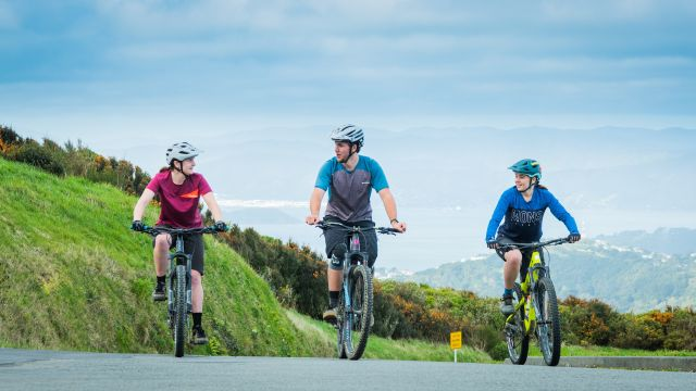 Three students on their mountain bikes, on a road, with mountain ranges and grass in the background.