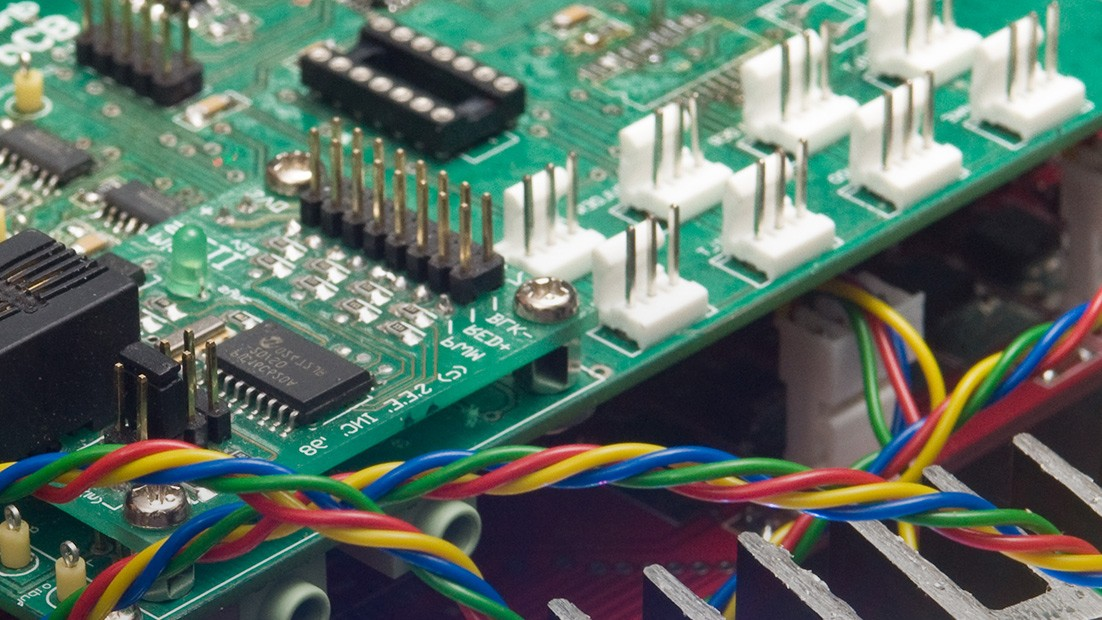 Close up image of a computer circuit board with coloured wires in the foreground.