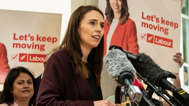 Prime Minister Jacinda Ardern giving a speech, with campaign posters in the background