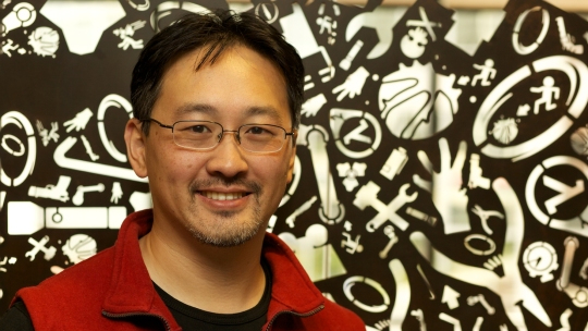 Computer programmer Milton Ngan in front of a printed backdrop.