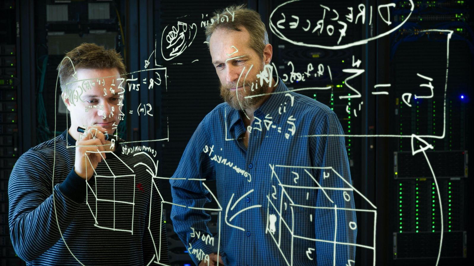 two scientists writing equations on a see-through white board