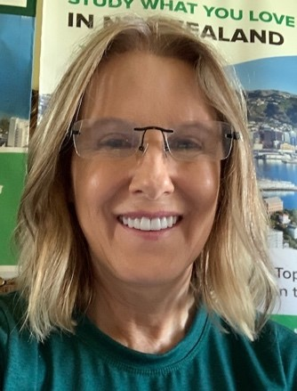 A woman smiling in a green top.