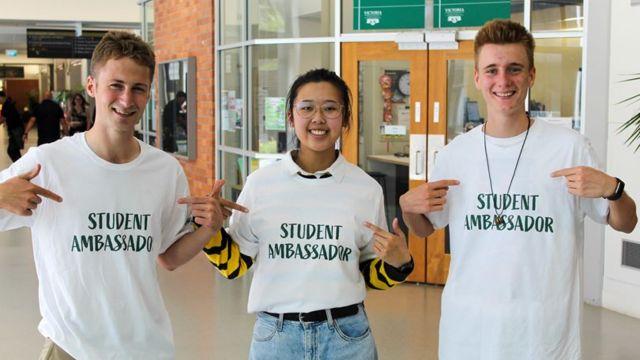 Student pointing at their t-shirts saying 'Student Ambassadors'.