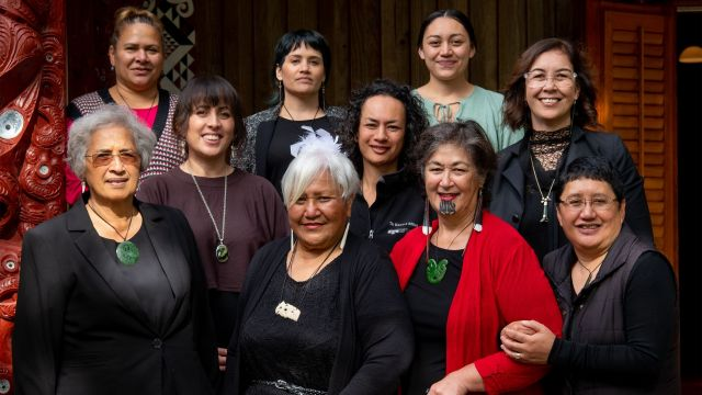 group of women out front of a marae with beautiful carvings