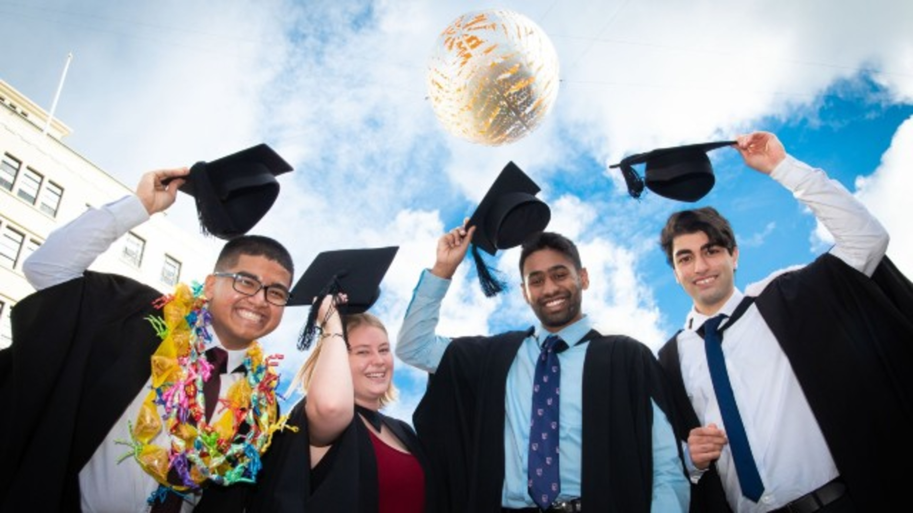 Three students holding their hats up at graduation.