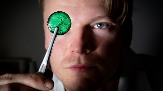 Dr Joe Schuyt in his laboratory holding a piece of fluorescent material