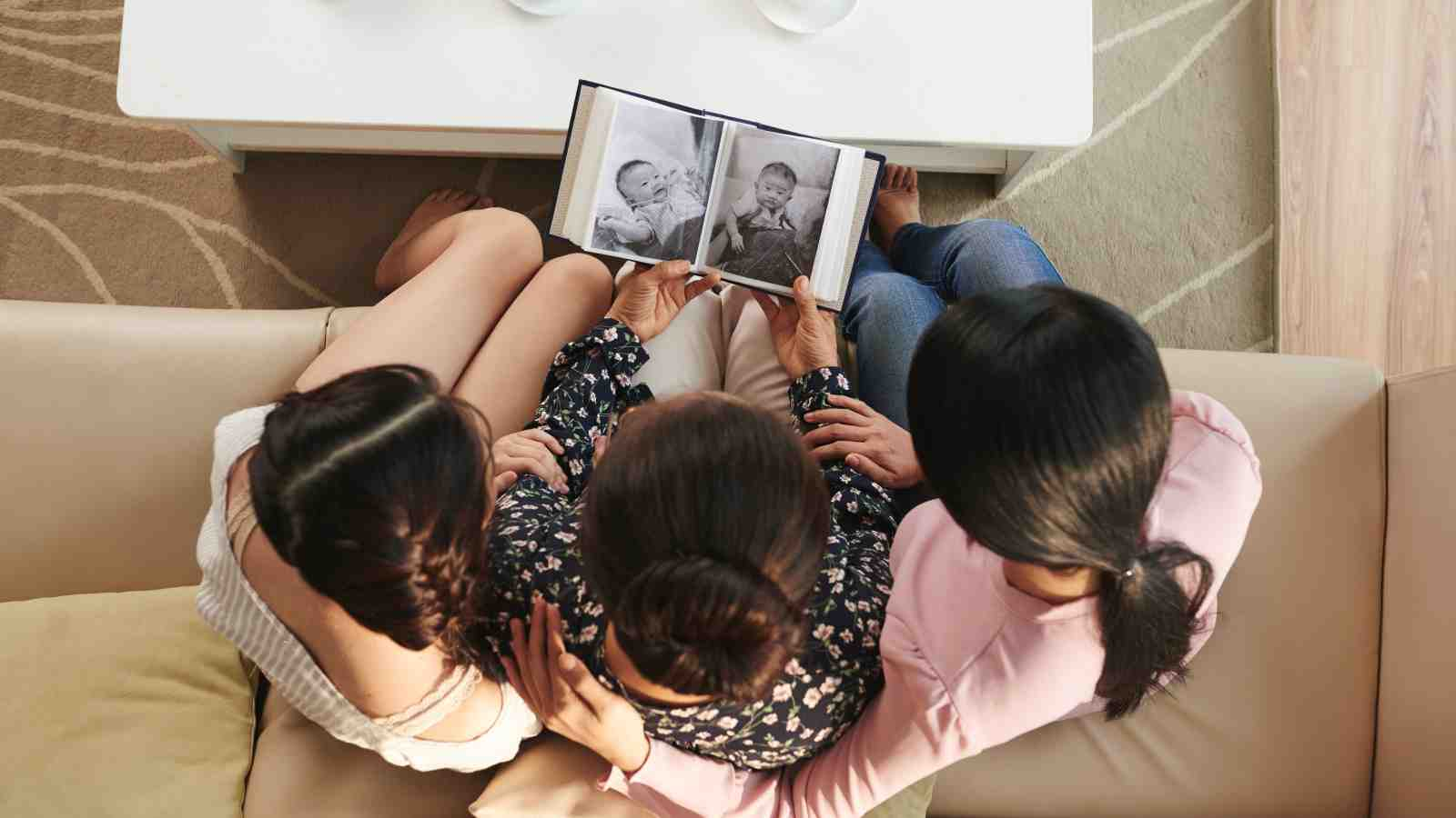 photo album being viewed by three women of different ages
