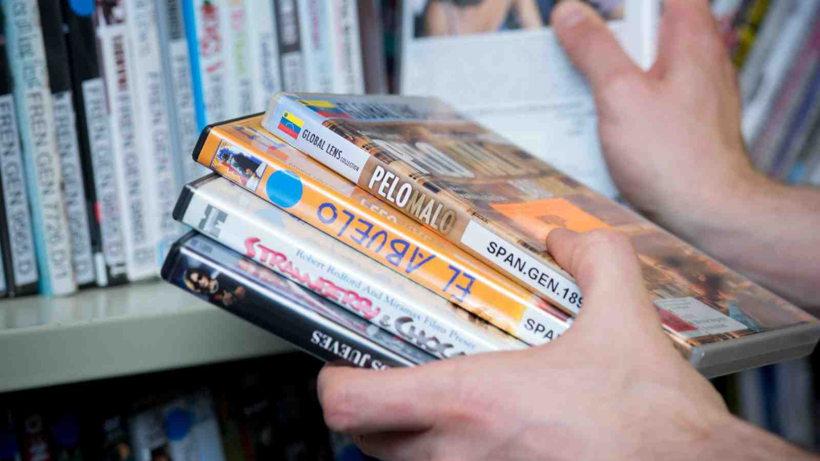 Te Waharoa library – a hand holds multiple dvd's in different languages.