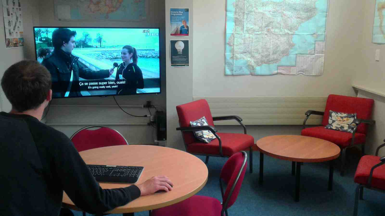 A student in a map room works at a table with a keyboard and mouse controlling a wall mounted television.