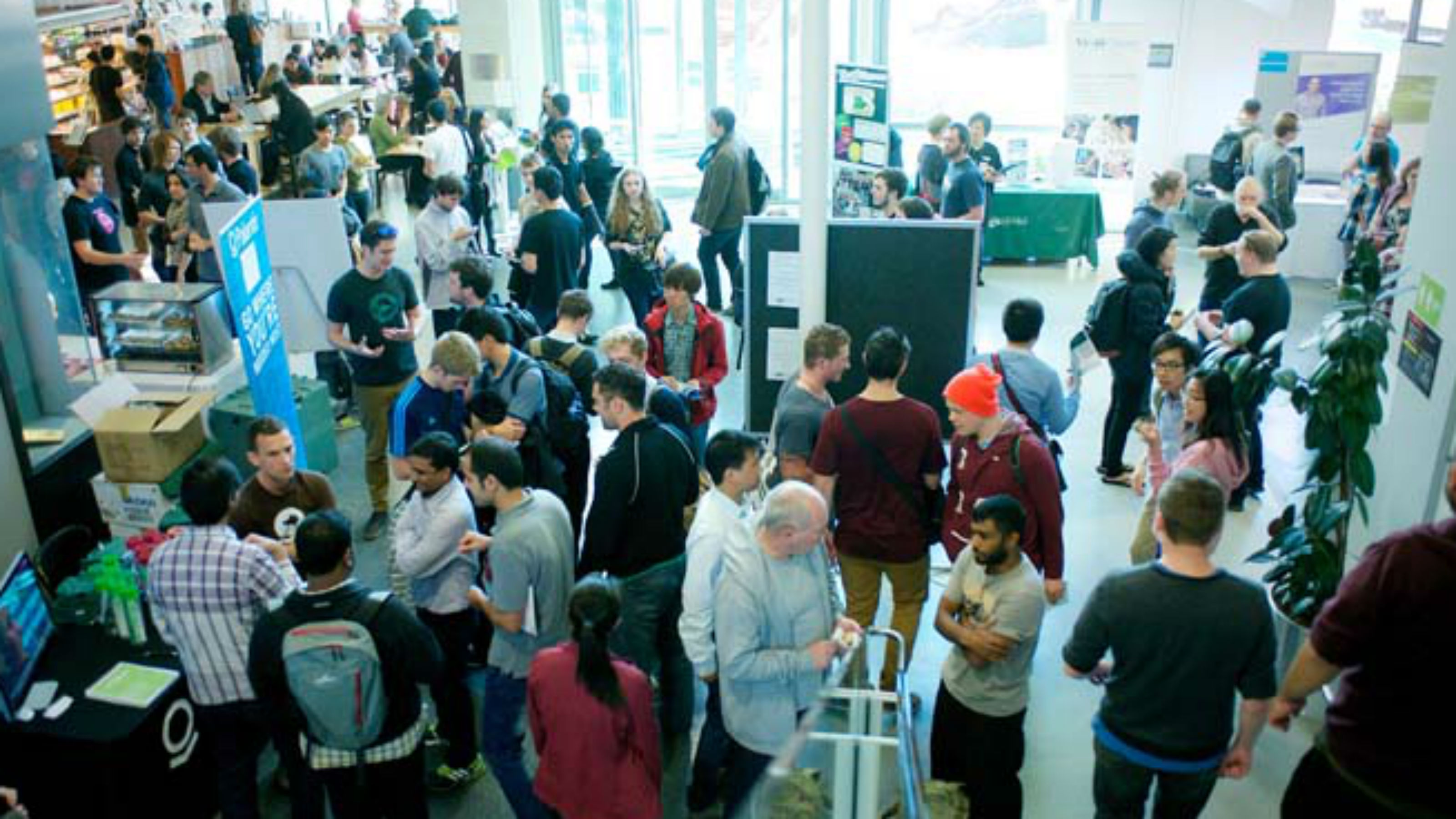 An image of many people in a large indoor room that has multiple banners and tables setup for an expo.