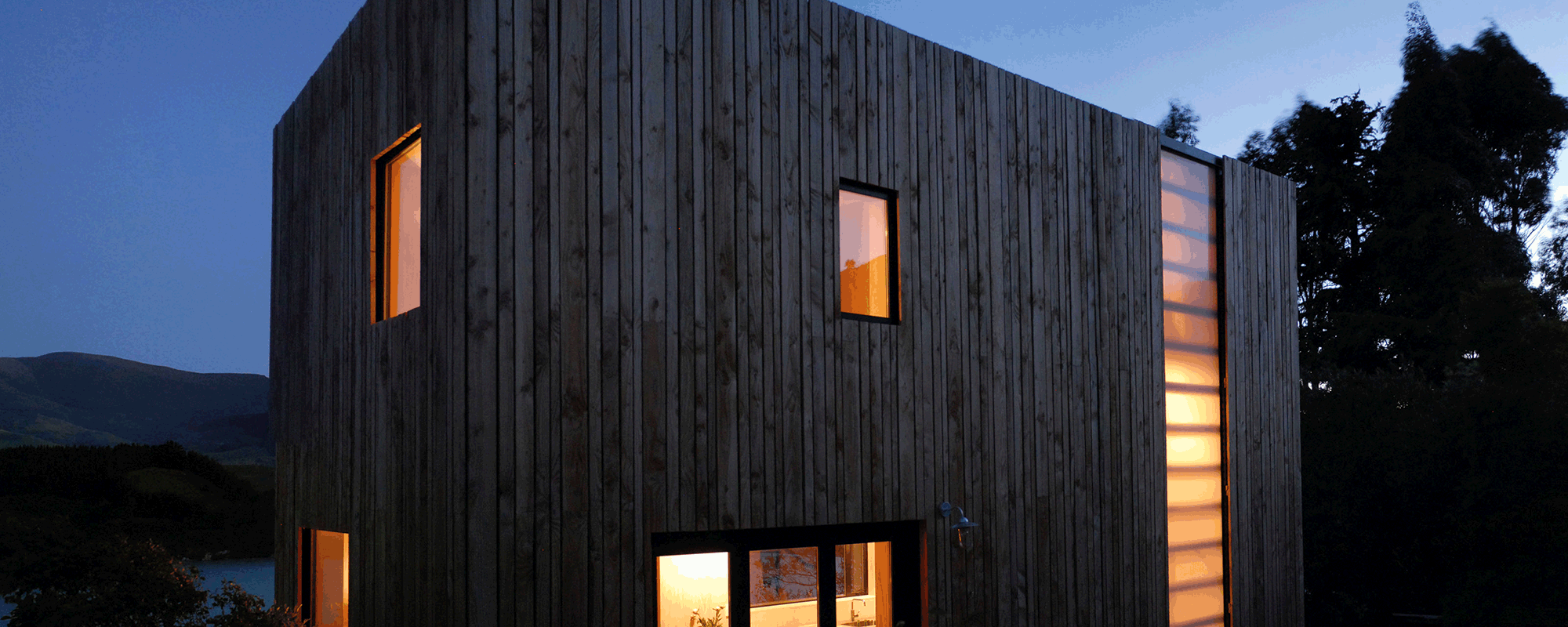 A small modern building, with vertical wood on the outisde taken at dusk, with warmly lit windows.