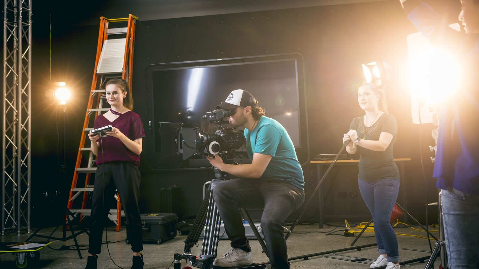 Students at work in a film studio, with a young man operating a camera in the middle and two females either side using other equipment.