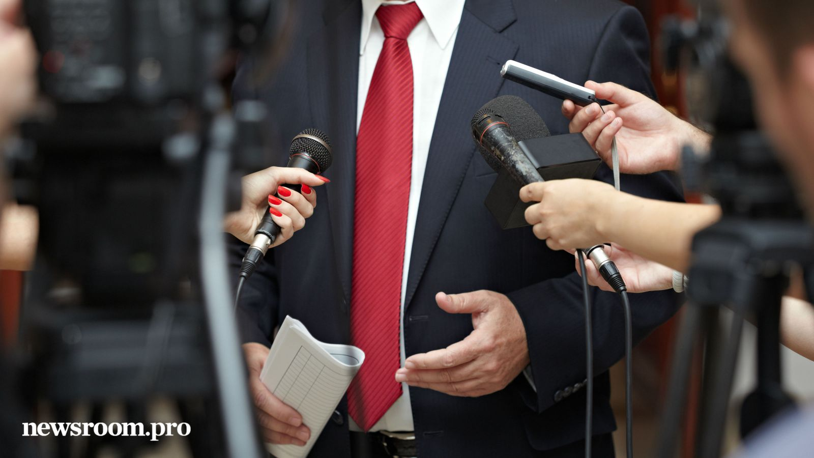 A man with a red tie is interviewed by various media.